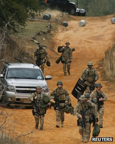 Law enforcement personnel walk away from the perimeter of the scene of a shooting and hostage taking in Midland City, Alabama, on 30 January 2013