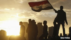 A protester holds an Egyptian flag as he stands on Kasr El Nile bridge, Cairo