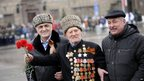Stalingrad veteran with carnations crosses the square before the parade - 2 February