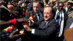 France's President Francois Hollande greets people in the centre of Timbuktu, 2 February 2013