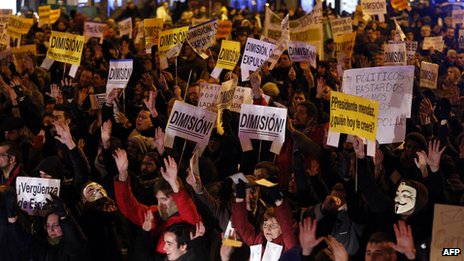 Protesters in Madrid holding banners reading 'Resign' (2 February 2013)