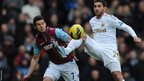 Angel Rangel holds off the challenge of West Ham's Matt Jarvis during Swansea City's Premier League visit to Upton Park.