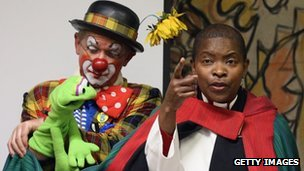 Rev Rose Hudson-Wilkin (R) on stage with clowns in full costume after
