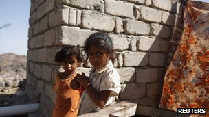Two little girls stand outside their family&#039;s hut in the mountainous village of al-Ma&#039;jalah, in the southern Yemeni province of Abyan