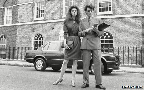 A 1980s couple pose in front of house and car