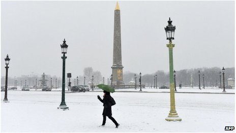A woman walks on the snow covered Place de la Concorde, Paris