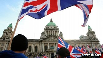 Loyalist protesters hold Union Flags during a demonstration outside Belfast City Hall