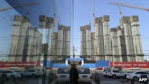A construction site of a residential compound is reflected on the glass facades of a office building in Taiyuan, Shanxi province, 15 January 2013