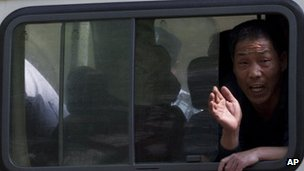 File image of a petitioner trying to draw public attention to his case yelling out from a police van in Beijing on 8 May 2012