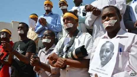 Somali journalists holding up the picture of their arrested colleague, Abdiaziz Abdinor Ibrahim, protest about his detention on 27 January 2013 in Mogadishu