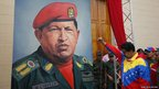 Nicolas Maduro raises his fist next to a painting of Hugo Chavez 