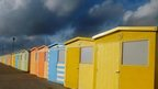 A row of colourful beach huts and above is a very dark blue and grey cloudy sky.