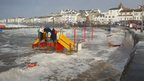 A children&#039;s play park by the beach is completely flooded, where the sea has come over the sea wall.