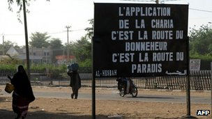 "Malians pass a billboard left by Islamist militants in the northern city of Gao, reading: ""Enforcing Sharia is the road to happiness, it is the road to paradise"""