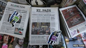 Copies of El Pais (centre) lie between other papers at a kiosk in Madrid, 24 January