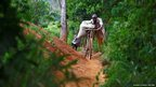 A gold miner uses a bicycle to transport a sack of sandy soil 