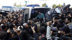 Mr Belaid's body is carried into an ambulance after he was shot in Tunis