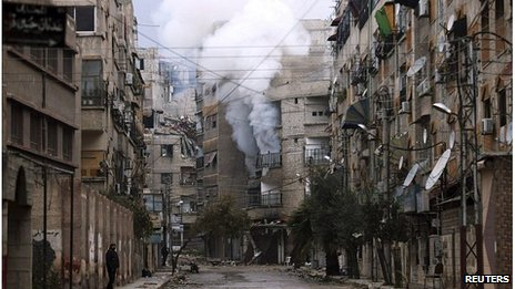 Smoke rises from a deserted street in Zamalka, Damascus
