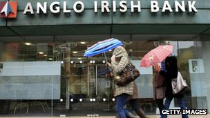 Pedestrians holding umbrellas pass in front of an Anglo Irish Bank branch