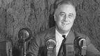 Franklin D Roosevelt sitting with microphones