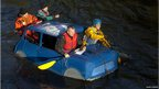Four men rowing in a car shaped raft