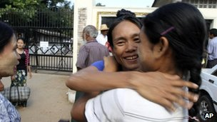 A Myanmar prisoner, centre, is welcomed by her relative outside Insein prison in Yangon, Myanmar