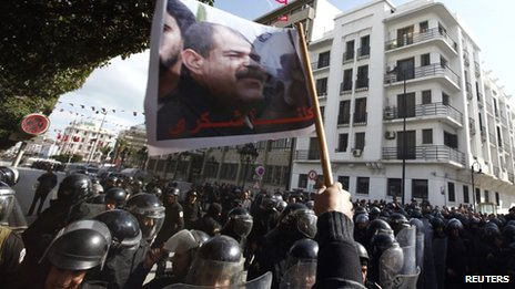 Tunisian protesters shout slogans during a demonstration after the death of opposition leader Chokri Belaid (pictured on flag), outside the Interior ministry in Tunis on 6 February 2013