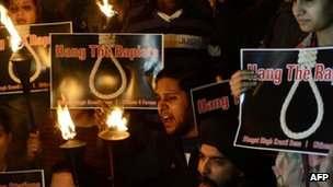 Indian students and activists shout slogans as they carry torches at India Gate following the gang-rape of a student in New Delhi.