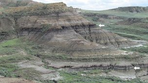 Rock layers near Jordan, Montana exposing the level (lower arrow) where the dinosaurs and many other animals and plants went extinct.