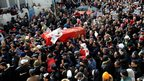 Chokri Belaid's coffin draped in a Tunisian flag being carried in a crowd in his funeral procession