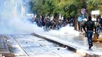 Protesters run away after police fire tear gas in Tunis