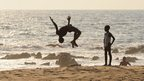 A teenager performing a somersault on Golden Beach in Monrovia, Liberia - Friday 1 February 2013