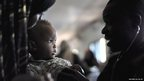 A Ugandan army medic with a mother and baby at a medical outreach centre in Mogadishu, Somalia - Wednesday 5 February 2013