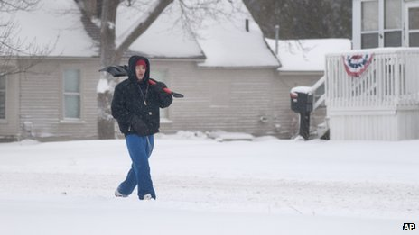 Donald Brodnex, 17, carries a shovel looking for driveways to clear in Saginaw, Michigan, on 8 February 2013