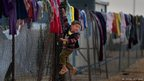 A boy hangs on a fence as Syrian refugees go about their daily business in the Zaatari refugee camp ,Jordan