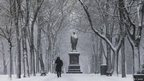 Jeannine Strampel walks past a statue of Alexander Hamilton along Commonwealth Avenue Mall in Boston, Massachusetts, on 8 February 2013