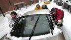 A group of men help push a sports car up a snow-covered street in the Old Port section of Portland, Maine, during a snowstorm, 8 February 2013