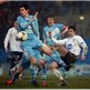 Ballymena United&#039;s Mark Surgenor attempts to block the clearance of Coleraine opponent Howard Beverland