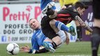 Glenavon&#039;s Andy Kilmartin and Declan Caddell of Crusaders hit the deck during the sixth round match at Seaview