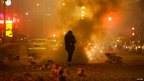 A man runs away after setting off firecrackers in central Beijing (10 February 2013)
