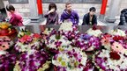 Worshippers rest near flower offerings at the Longshan temple in Taipei (10 February 2013)
