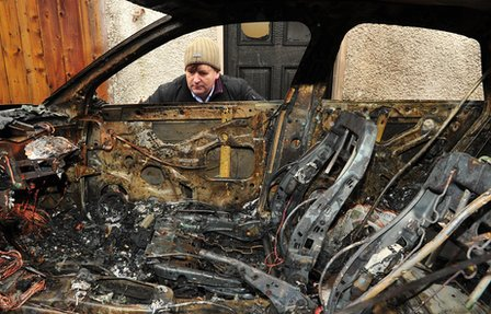Willie Frazer looks at the interior of the burnt-out car