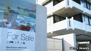 A for sale sign in front of an apartment block in Australia
