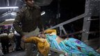 Police carry a pilgrim injured in a stampede at a railway platform at the main railway station in Allahabad, India, Sunday, Feb. 10, 2013