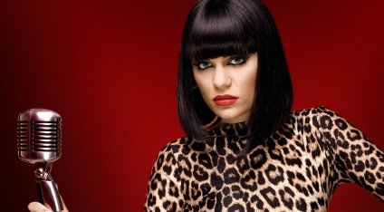 Jessie J in a publicity still for The Voice UK. She is wearing a leopard print top and holding a microphone.
