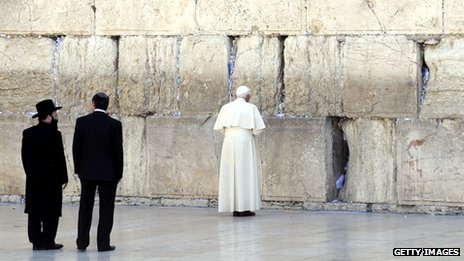 Pope Benedict praying at the Western Wall in Jerusalem as two Israeli men look on, 12 May 2009