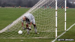 Goalkeeper fishes a ball out of the back of the net