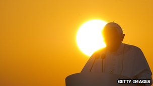 Pope preaching against background of sunset