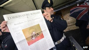Policeman holds a copy of the Vatican&#039;s newspaper