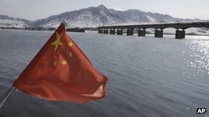 A Chinese flag is hoisted near the Hekou Bridge (R) linking China and North Korea, 7 February 2013